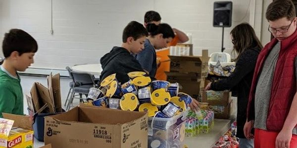 Middle school students preparing snack packs