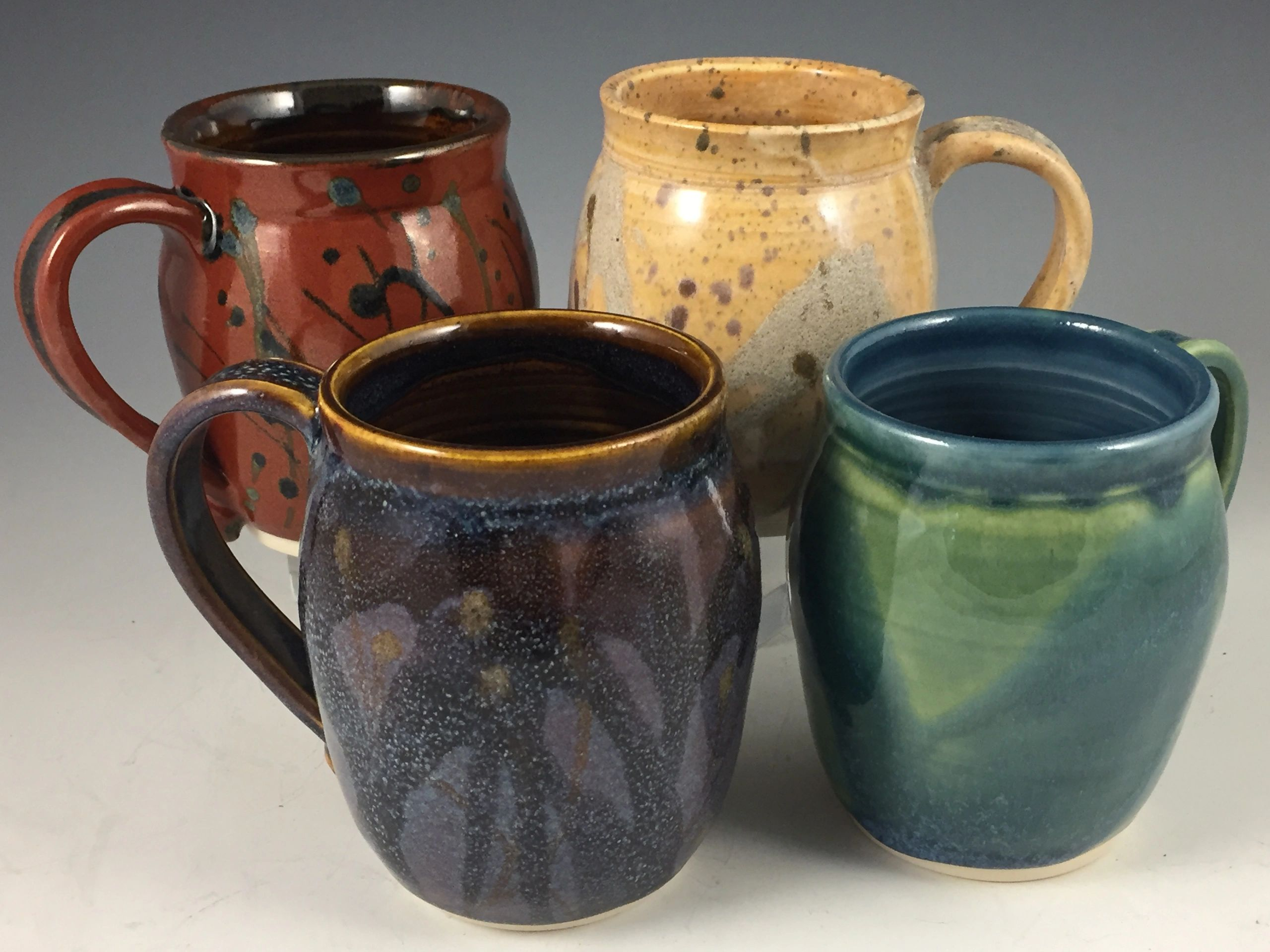 Handmade functional ceramic mugs, wheel-thrown of white stoneware clay and high fired.