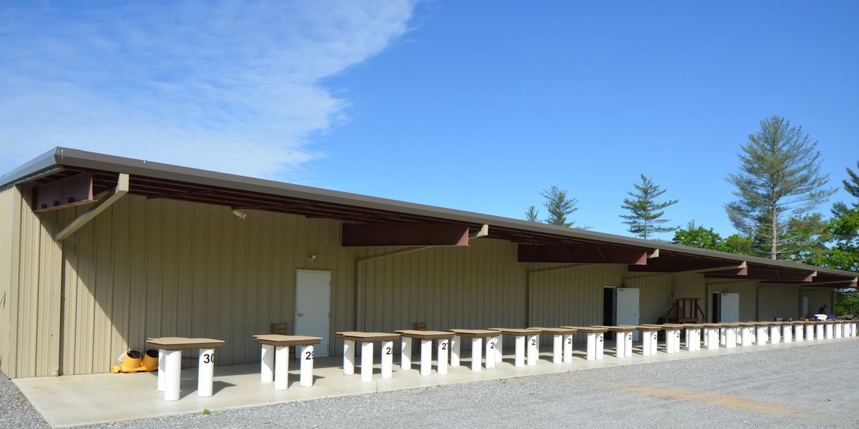 Club House with in-door bathrooms with 30 benches pointing down a 300-yard rifle range.
