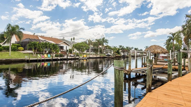 A view of a navigable, gulf-access canal in Cape Coral with docks and palm trees in view.
