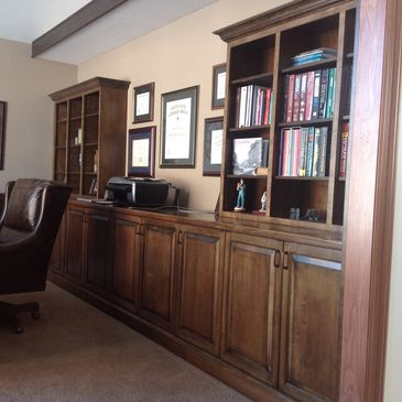 Stained maple cabinetry in a study, including open book case cabinets and a fold down desk.