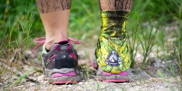 Trail runner's feet covered in mud, one gaiter is on & one is off showing how well the gaiters work