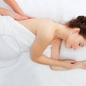 Prenatal Massage - pregnant women laying on her side smiling getting a massage