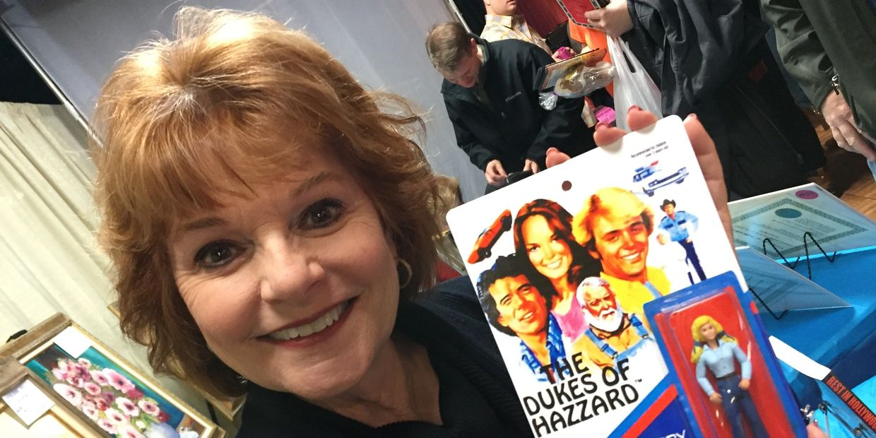 Dorothy Best holding an action figure of her character from the Dukes of Hazzard.