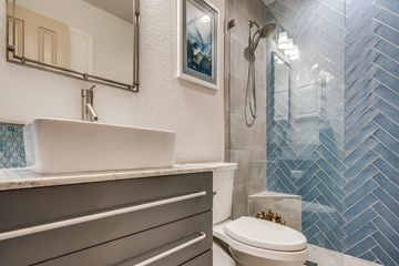 Seamless walk in shower with blue subway tiles and marble floating vanity