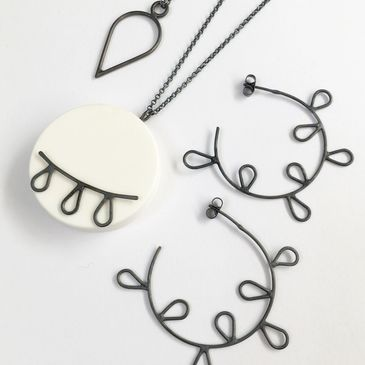 White resin and oxidised silver pendants and earrings.