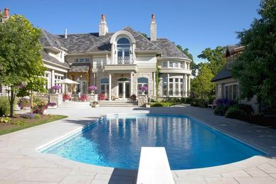 Very large white mansion with gorgeous pol in back yard