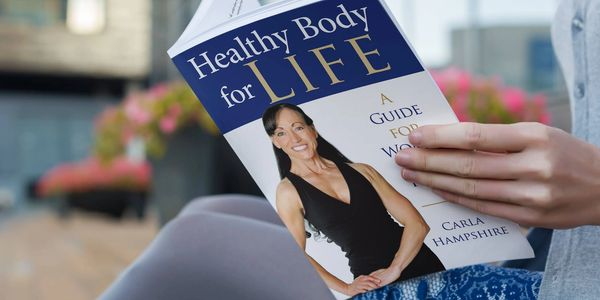 Woman reading book about health for women over 40