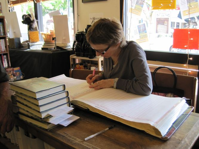 Writing my name in a very special book for authors at Mysterious Bookstore in  Los Angles.  Felt ver