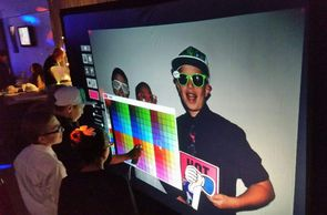 Screen projects a virtual wall for guests to use interactive pens to decorate their photo.
