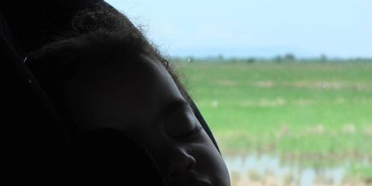 Napping in her car seat on the road in DR