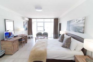 A Standard Room of Point Hotel and Spa with Bed Chairs, Tv, Tables, Mirror and A majestic Ocean View