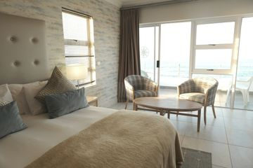 A Suite Rooms of Point Hotel and Spa with bed, chairs, and a table with Ocean View