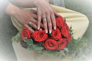 Wedding Rings on the hand of Bride and Groom along with a Bouquet of Red Roses