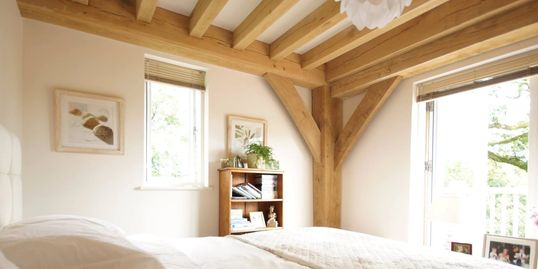 BAARN pre-fab house bedroom with exposed structural green oak frame including ceiling joists
