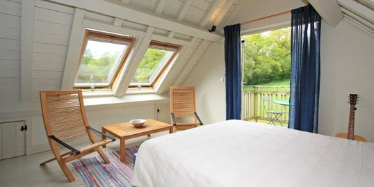 Sustainable BAARN kit eco-house loft bedroom with painted softwood exposed structural frame