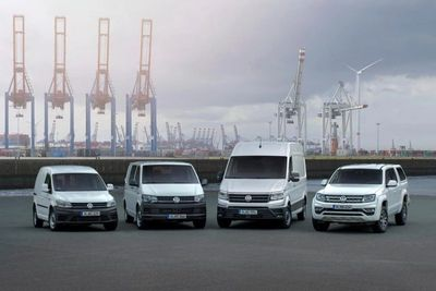 Fleet of 4 small vans aligned with a port in background