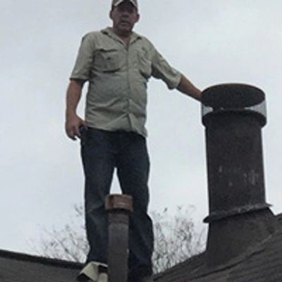 Brad Leland on the roof inspecting the chimney flashing for a possible leak due to water stains