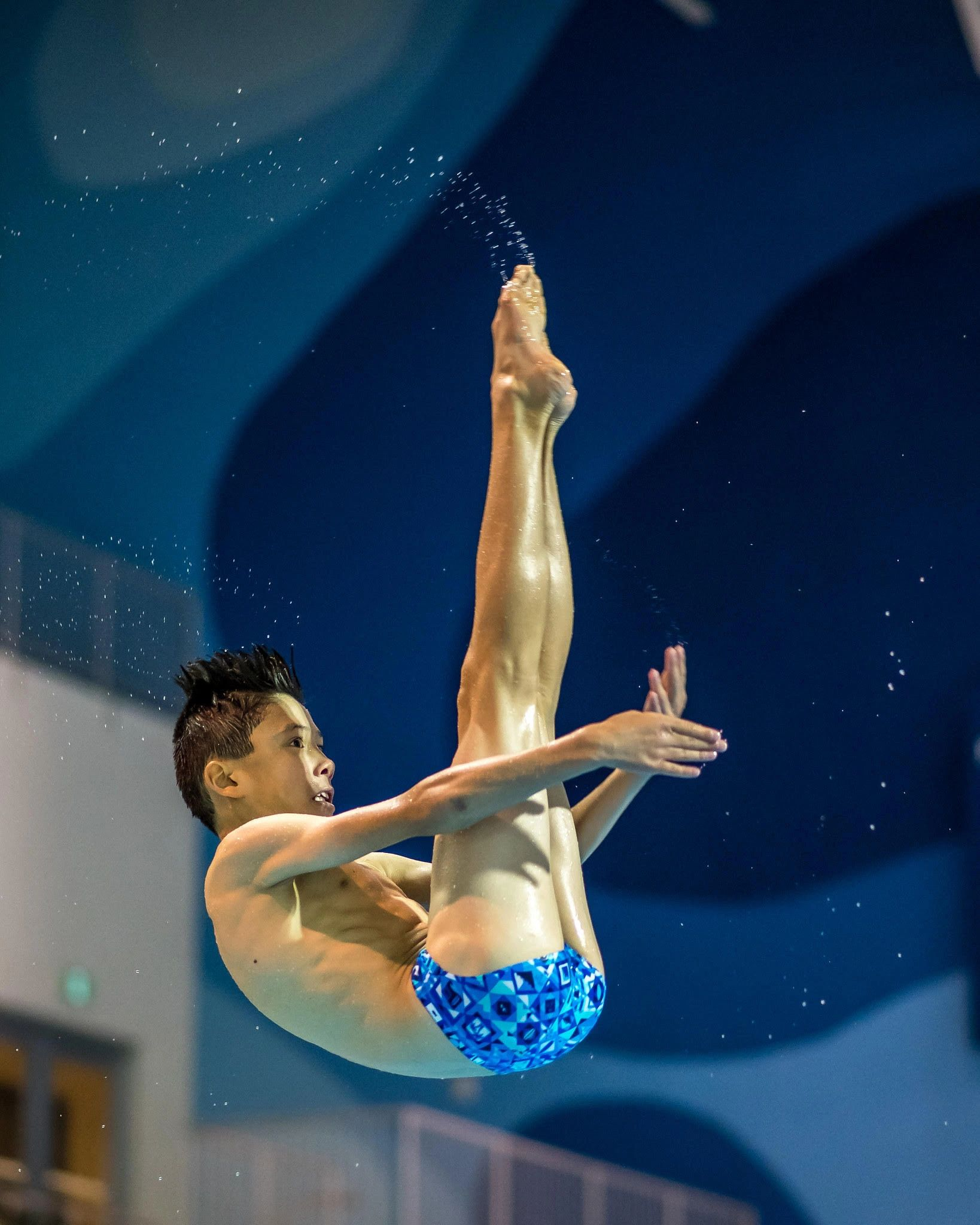 Diver spins through the air in pike position.