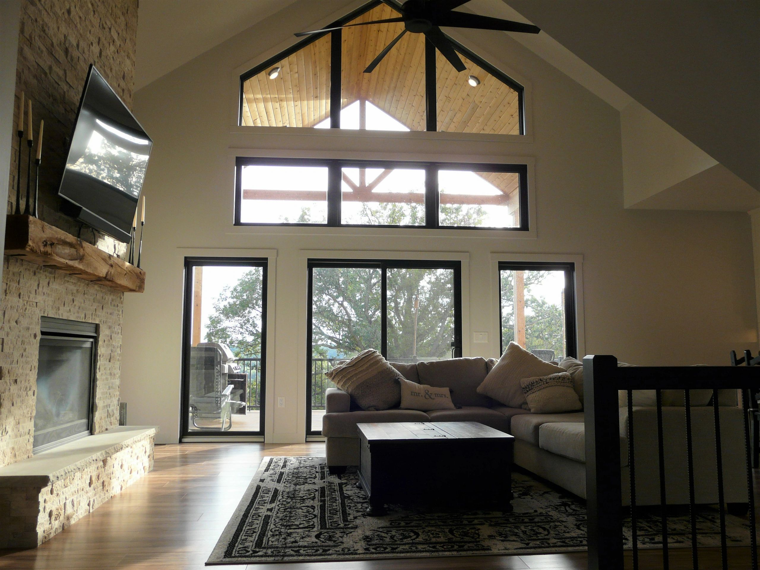Custom home design of great room with a frame windows and covered deck.