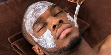 man getting facial mask applied