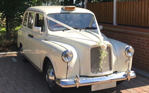 white taxi with wedding ribbons