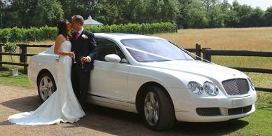 couple kissing in front of Bentley Car
