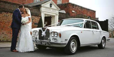 couple kissing in front of wedding carRolls Royce Silver Shadow Saloon