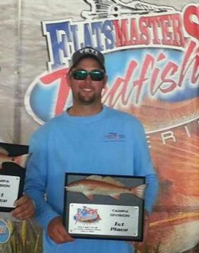 Captain John with a 1st place trophy in a professional redfish tournament