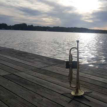My Flip Oakes Wild Thing Trumpet on a pier overlooking a beautiful lake as the sun sets.
