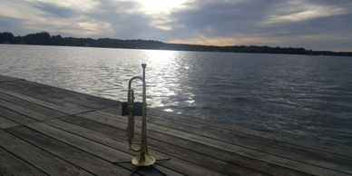 My Flip Oakes Wild Thing Trumpet on a pier overlooking a beautiful lake as the sun sets