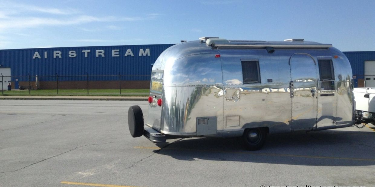 A very shiny Airstream trailer in front of the Airstream factory in Jackson Center, Ohio.