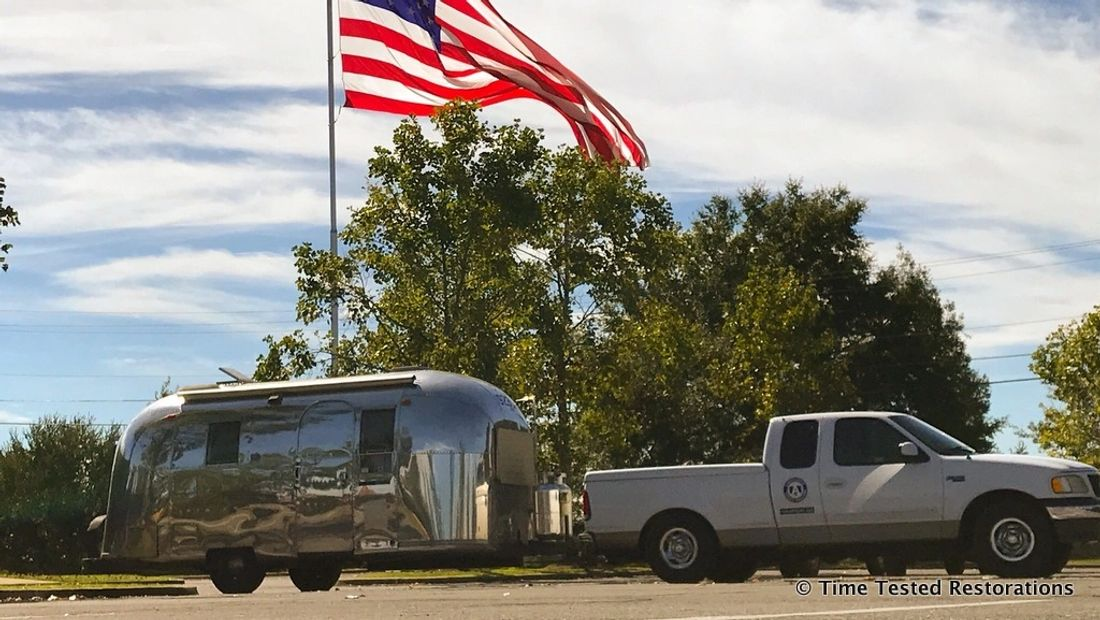 A shiny Airstream travel trailer and pickup truck under larger American flag.