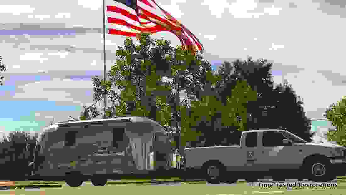 A shiny Airstream travel trailer and pickup truck under a very large American flag.
