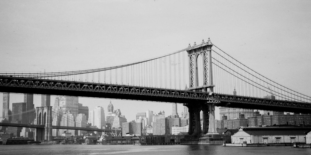 Vintage black and white image of the Manhattan Bridge in New York City.  Bell and Howell trave