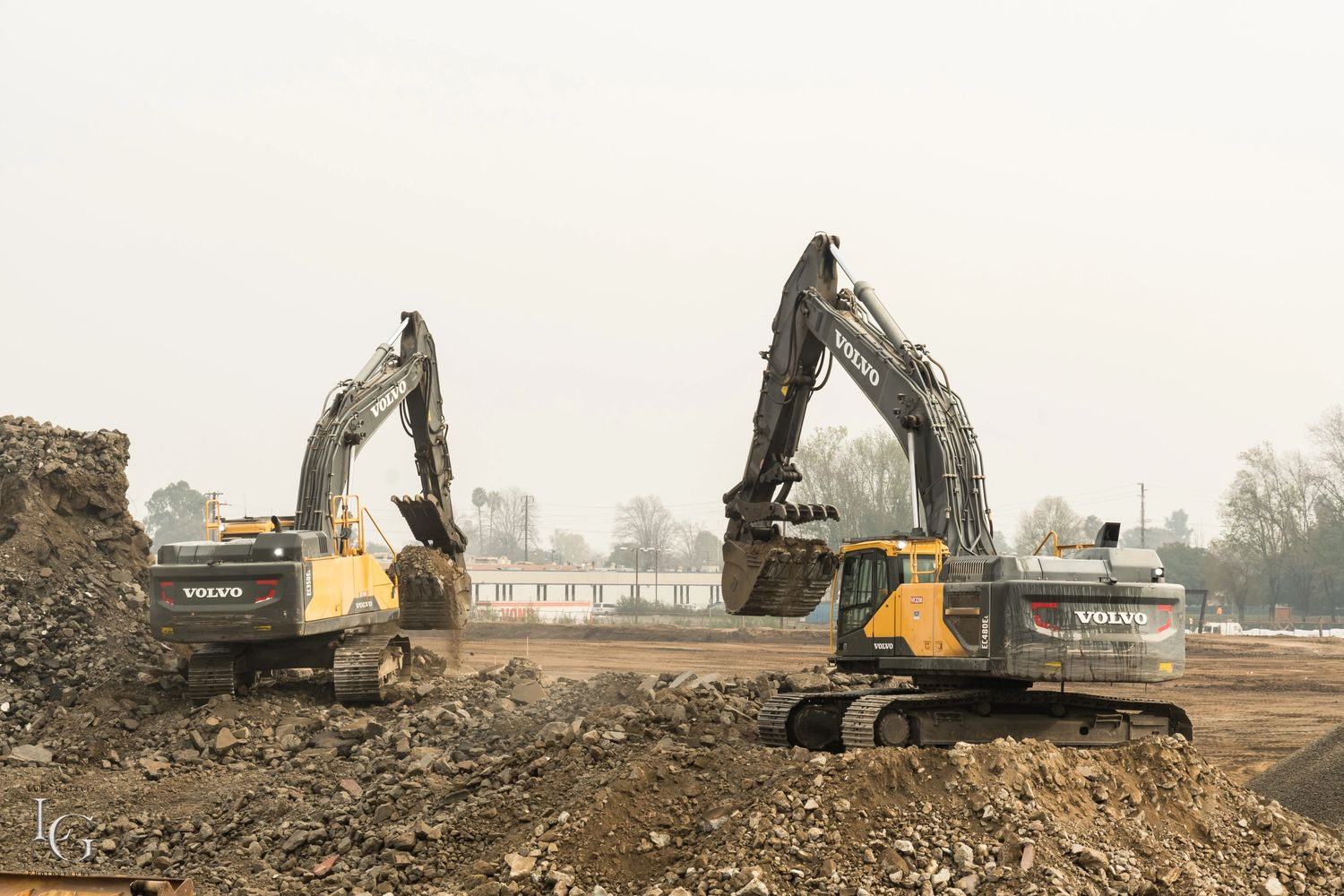 Demolition site clearing, concrete recycling, excavator team work, Volvo Excavator