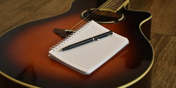 songwriting essentials, guitar, notebook, pencil