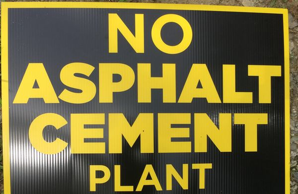 A brown sign trimmed in yellow with the words in yellow that says. :No Asphalt Cement Plant.