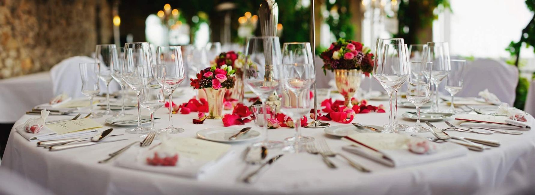 Elegantly organized table for an event with a white map flower bouquets, wine glasses and cutlery