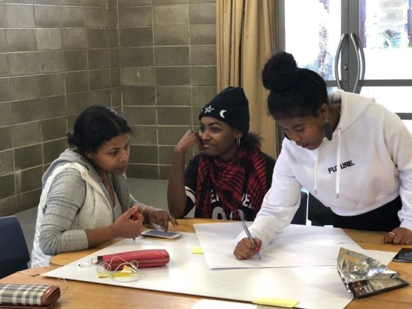 Three young female immigrants engaging in a workshop