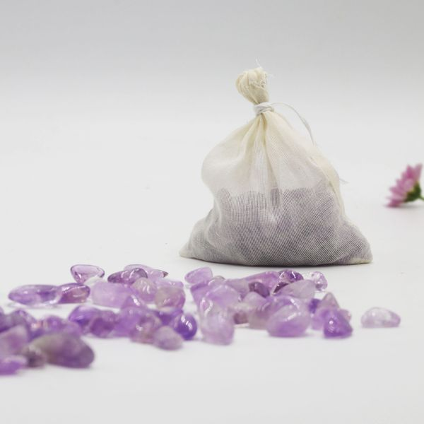 A white fabric bag with loose Amethyst crystals in-front of the bag