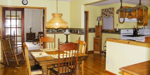 Dining room with full vintage dining table, knotty pine floors. Looks into kitchen and living room