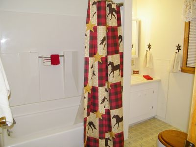 Picture shows full downstairs bath with shower, tub, and red and black plaid horse shower curtain