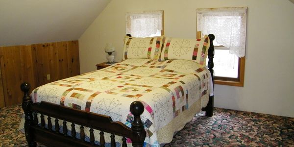 Upstairs master bedroom with pretty quilted queen bed, sloped ceiling, and two windows