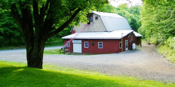 Picture shows red dairy barn with additional driveway parking and trees in in the background