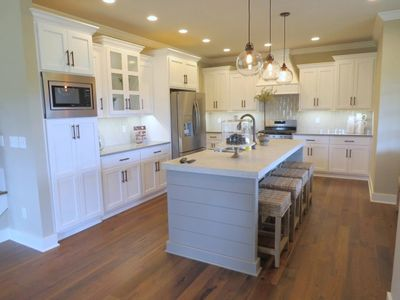 Finished kitchen with staggered wall cabinets and shiplap island