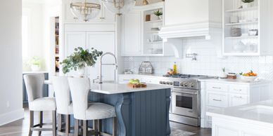 White kitchen cabinets with open shelves and stove hood. Custom navy island.