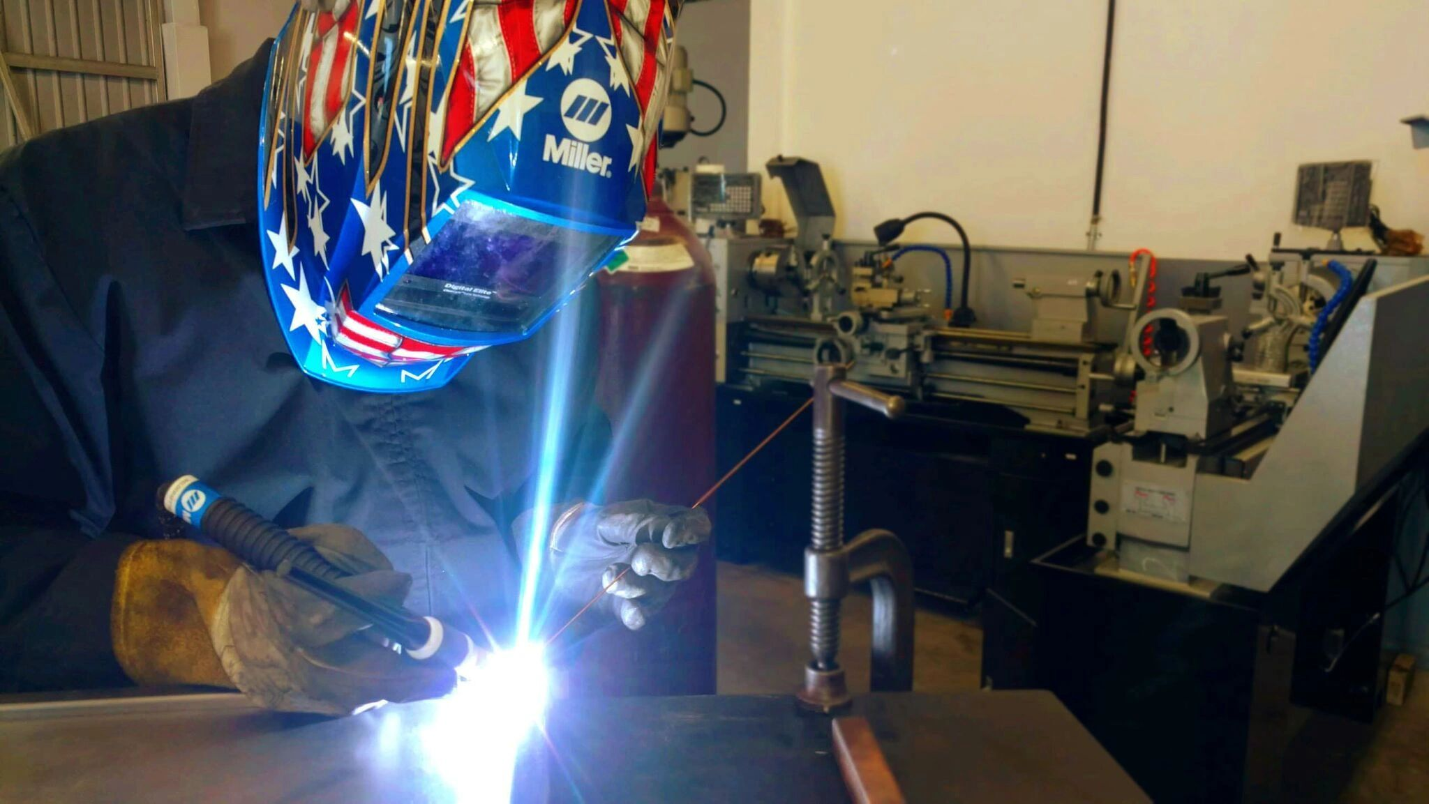 A sheet metal fabricator is working on a project for metal fabrication class.