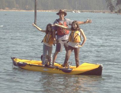 3 people standing on a kayak