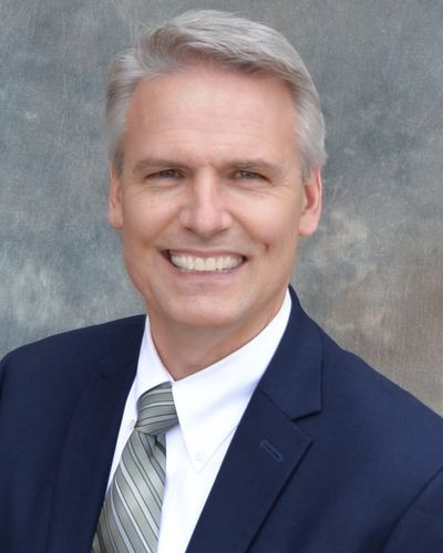 Ken Neal Realtor poses for his head shot in his real estate business